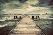 Old wooden jetty, pier, during storm on the sea. Dramatic sky with dark, heavy clouds. Vintage