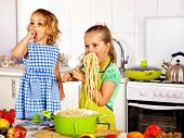 Children  eating spaghetti at kitchen.