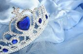 stock photo of tiara  - Toy tiara with diamonds and blue gem like a princess crown on blue satin princess robe - JPG