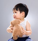 Adorable baby boy play with doll bear