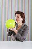 Businesswoman blowing a balloon at the office