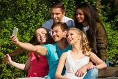 Multi ethnic group of sporty teenage friends in a park taking selfie