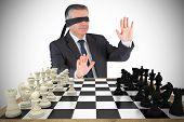 Composite image of mature businessman in a blindfold with chessboard
