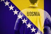Bosnia football player holding ball against bosnia national flag