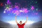 Excited football player cheering against fireworks exploding over football stadium