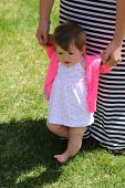 Adorable little baby girl learning to walk