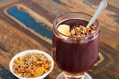 Acai In Glass With Muesli Banana On Wooden Table