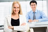 Successful business woman sitting with her collegue in background at office