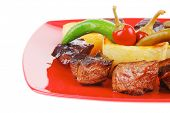 european food: grilled meat goulash on red plate with hot peppers, capers and olives oil, and bbq sa