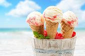 Close up of raspberry ripple ice creams with beach blur background