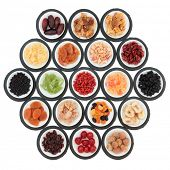 Large dried fruit selection in white bowls on slate rounds over white background.