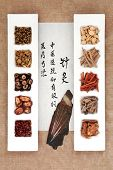Chinese herbal medicine with acupuncture needles and calligraphy script. Translation describes acupuncture chinese medicine as a traditional and effective medical solution.