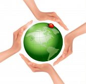Hands holding a green earth with a ladybug.