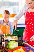 Mother showing daughter how to cook in domestic kitchen