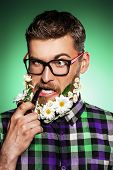 picture of peace-pipe  - Funny young man in glasses and a beard of flowers smoking a pipe - JPG