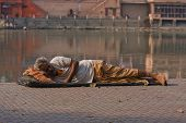 Haridwar, India - Nov 8: An Unidentified Homeless Man Sleeps On The Sidewalk Near The River Ganges O