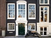 Amsterdam, Netherlands - March 19, 2014: Black Vespa Scooter Stands Parked Near Old Living House In