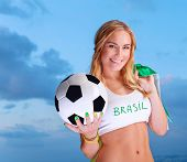 Happy fan of Brazilian football team, cheerful pretty girl on stadium cheering in support, holding u