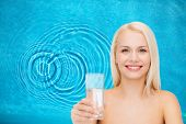 health and beauty concept - closeup of young smiling woman with glass of water