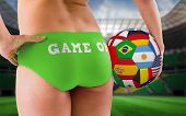Fit girl in green bikini holding flag football against large football stadium with brasilian fans
