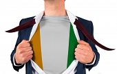 Businessman opening shirt to reveal ivory coast flag on white background