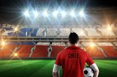 Chile football player holding ball against stadium full of chile football fans