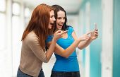 technology, friendship and people concept - two smiling teenagers pointing finger at smartphone