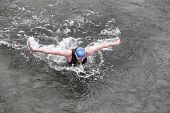 dynamic and fit swimmer in cap and wetsuit breathing performing the butterfly stroke in dark ocean w