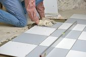 Tiler install ceramic tiles on a floor