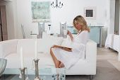 classy woman in white room drinking coffee reading book or magazine