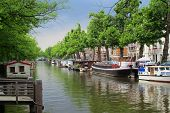 stock photo of houseboats  - Houseboats moored along a beautiful canal in Amsterdam.