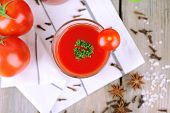 Tomato juice in glass and fresh vegetables on napkin on wooden background