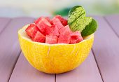 Slices of watermelon in melon bowl on wooden table on natural background