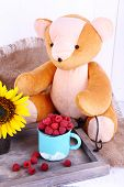Toy bear and mug of raspberries on wooden tray on sackcloth on wooden wall background