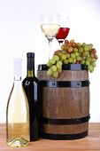 Wine in goblets and grapes on barrel and wine in bottles on wooden table on white background
