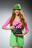 Woman in colourful dress holding movie board