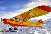 Yellow Red Airplane At The Mountain Slope In Swiss Alps