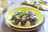 Black pasta with salmon and red caviar in cream sauce