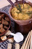 Fondue, bowl of rusks, biscuits, spice and garlic on wicker mat on wooden background