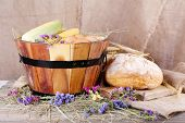 Big wooden basket with eggs, dried flowers, bread and maize on sacking background