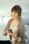 Thoughtful girl sending text message on smartphone