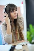 Young woman at work using headphones in front of desktop