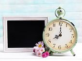 Beautiful flowers with clock and chalkboard on table on light blue background