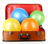 Pile of balloons of different colors in old suitcase, isolated on white