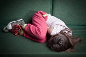 picture of girlie  - little girl curled up in fetal position on a couch protecting herself from danger or cold - JPG