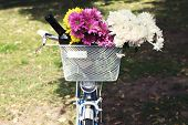 Bicycle with flowers and bottle of wine in metal basket closeup