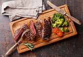 Sliced Medium Rare Grilled Beef Steak Ribeye With Broccoli On Cutting Board On Wooden Background