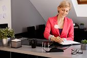 Smiling young businesswoman sitting at desk in office, writing notes.