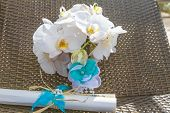 beautiful wedding bouquet from white orchids and wedding certificate on natural background