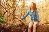 Woman Sitting On Fallen Tree Trunk